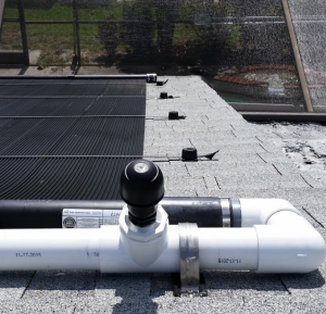 A Vacuum Relief Valve installed at the highest point in this solar pool heating system relieves negative air pressure from water draining from the panels.